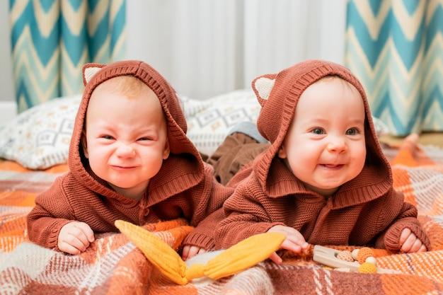 Забавные близнецы лежат на пледе дома в кофточках с ушками животных