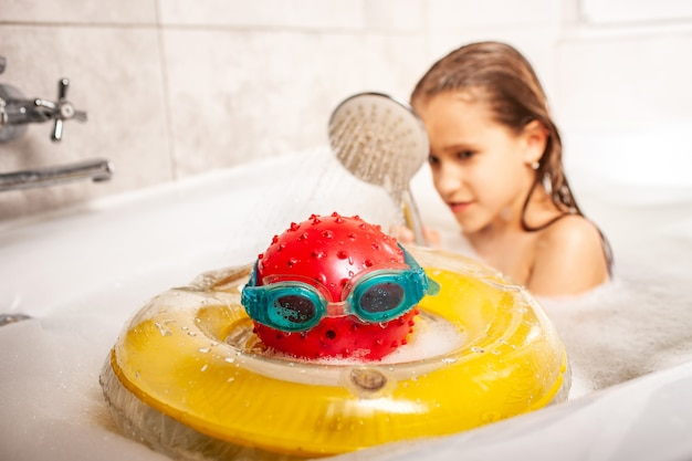공으로 만든 머리를 샤워 하는 재미 있는 작은 미확인된 소녀