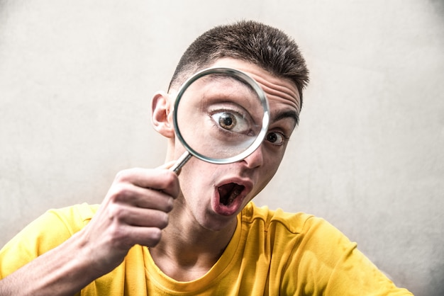 Funny looking boy looking inside a magnifying glass