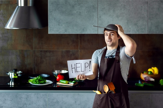 金属ふるい、フライパン、木製の台所用品、エプロンを調理しようとするとおかしな敗者の男性男性が失敗し、灰色のモダンなロフトキッチンで助けが必要です。キッチンのコンセプトに失敗した学士。