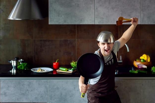 忍者を調理しようとするポーズで頭のフライパンと木製の台所用品に金属鍋で面白い敗者男性が失敗し、灰色のモダンなロフトキッチンで叫ぶ。キッチンのコンセプトに失敗した学士
