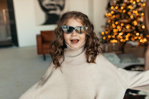 Bambina adorabile divertente con riccioli che indossa un maglione lavorato a maglia oversize e occhiali da sole che ballano davanti all'albero di natale