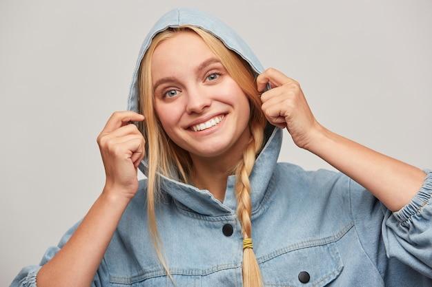 三つ編み、手はフードを保ち、幸せを感じ、広く笑顔で面白い素敵な美しい金髪の若い女性