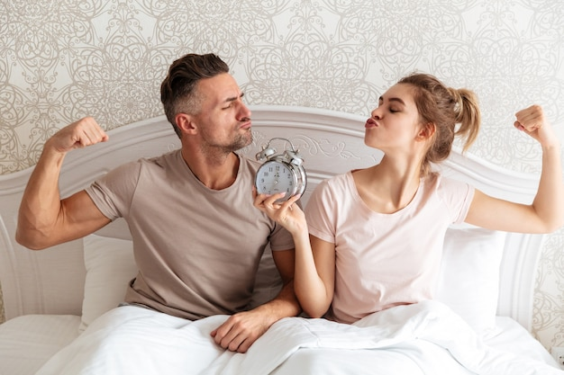 Funny lovely couple sitting together on bed with alarm clock