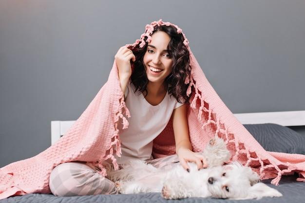 モダンなアパートメントのベッドの上の小さな白い犬と遊んでピンクの毛布の下のパジャマで幸せな若い女の面白い素敵な家の瞬間。笑顔、陽気なムード、ポジティブさを表現。