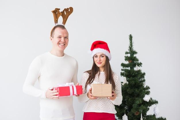 クリスマス ツリーの近くの面白い愛情のあるカップル。男は鹿の角、女はサンタ帽子。