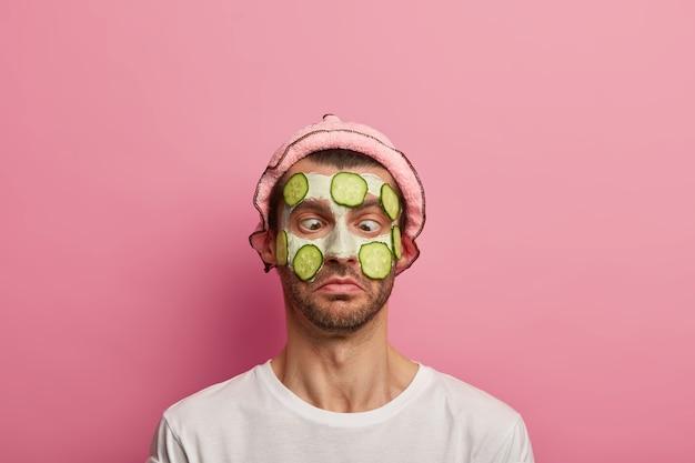 Il modello maschile divertente ha un'espressione comica, incrocia gli occhi, indossa una maschera all'argilla e fette di cetriolo sul viso, un morbido copricapo
