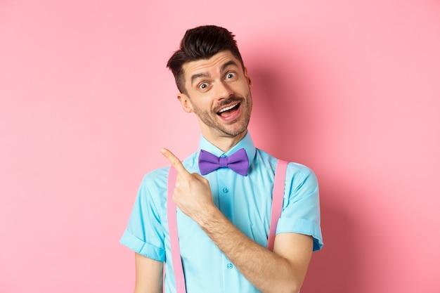 Забавная мужская модель в галстуке-бабочке, наклоняет голову и указывает пальцем влево, приглашая посмотреть, зацените жест, показывая рекламу на розовом.