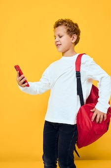 Funny male teen in white sweatshirt mobile cell phone red backpack yellow background
