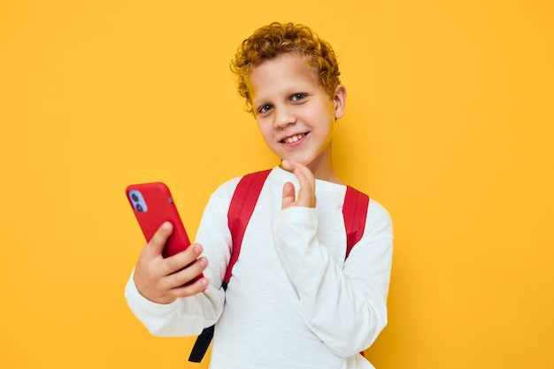 Funny male teen with a red backpack calls on the phone isolated background