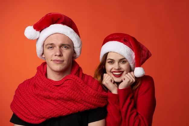 面白い男と女のクリスマスサンタ帽子友情赤い背景