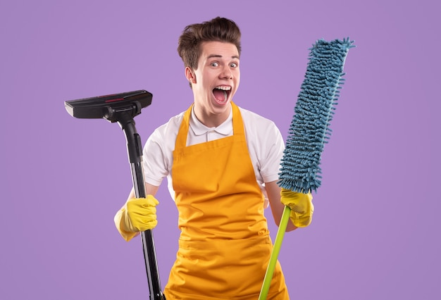 Funny man in apron and gloves showing vacuum cleaner and mop and looking with opened mouth during cleaning routine