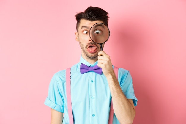 Funny man in bowtie look through magnifying glass squinting and making silly faces standing on pink ...