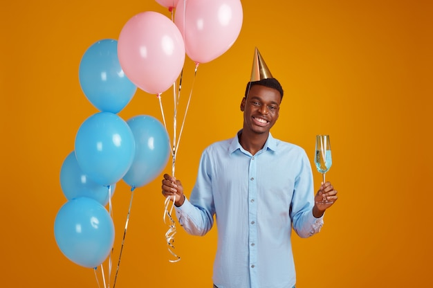 Funny man in cap holding a glass of beverage, yellow background. smiling male person got a surprise, event or birthday celebration, balloons decoration