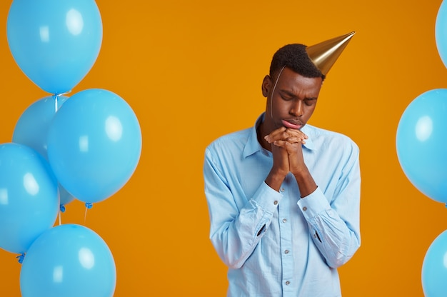 Funny man in cap. male person got a surprise, event or birthday celebration, blue balloons decoration