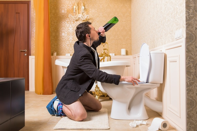 おかしな男は便器に座ってアルコールを飲みます。豪華なバスルームのインテリア