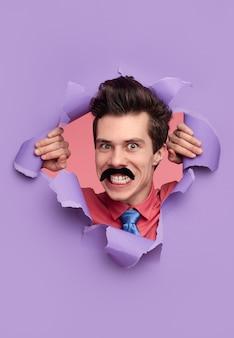 Забавное лицо человека с поддельными усами, рвущими дыру в бумаге