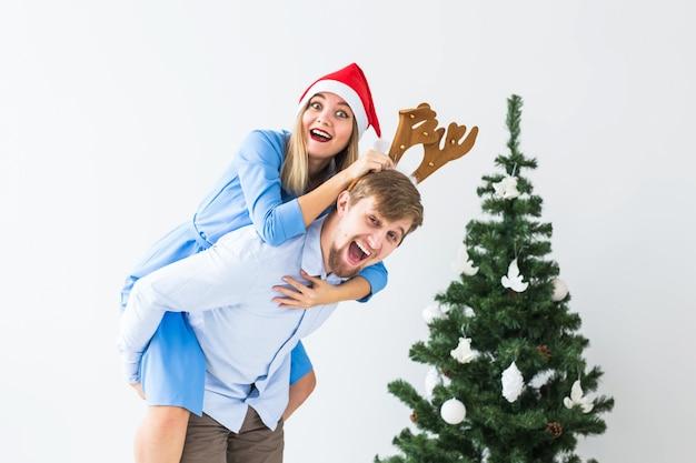 彼らが家でクリスマス休暇のためにサンタの帽子をかぶっている間、彼の妻に便乗を与えるおかしな男。