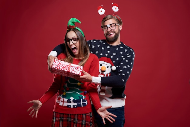 クリスマスの贈り物を与える面白い男キャンディケインの隣に立っているカップル