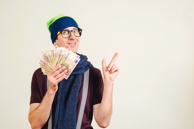 Funny man in glasses wearing header holding money and pointing on empty copy space. male nerd with banknotes on white. man present a product or an idea