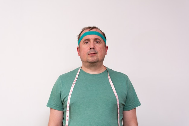 A funny man in a green bandana and a t-shirt with a measuring tape around his neck