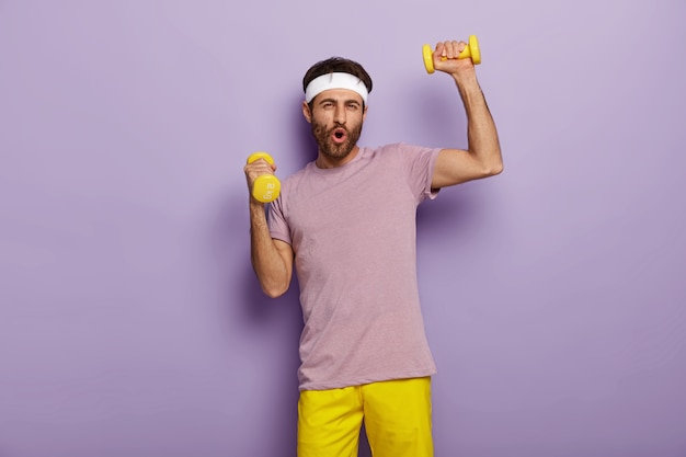 Funny man has fun, exercises with dumbbells, dressed in active wear, motivated for healthy lifestyle, has regular training in morning