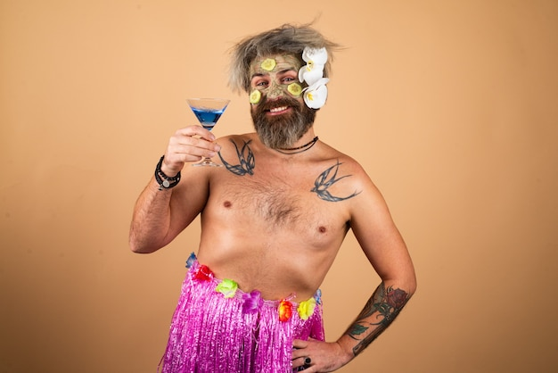 Funny man in hawaii male model with clay mask and cucumber slices on face man having cosmetic moistu...