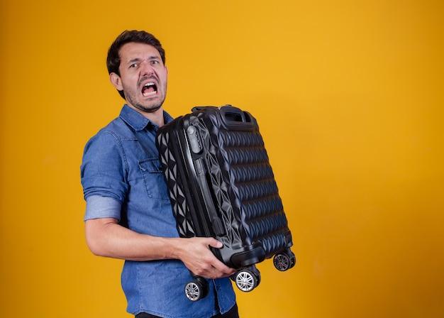 重い旅行かばんを持っている面白い男。黄色の背景に