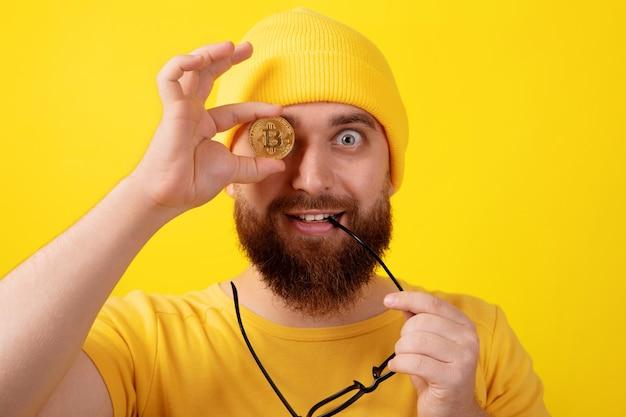 노란색 배경 위에 비트코인을 들고 있는 재미있는 남자