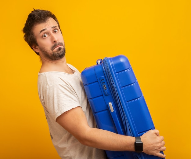 Funny man holding a heavy travel bag on yellow