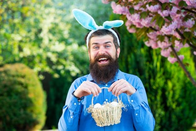 부활절 달걀을 사냥하는 재미있는 남자 부활절 남자의 초상화는 부활절 달걀 봄 방학이 있는 바구니를 들고 있다