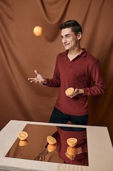 赤いシャツを着たおかしな男が鏡の近くでオレンジを投げる