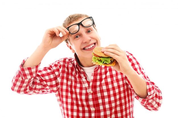 Смешной человек в очках ест гамбургер, изолированных на белом