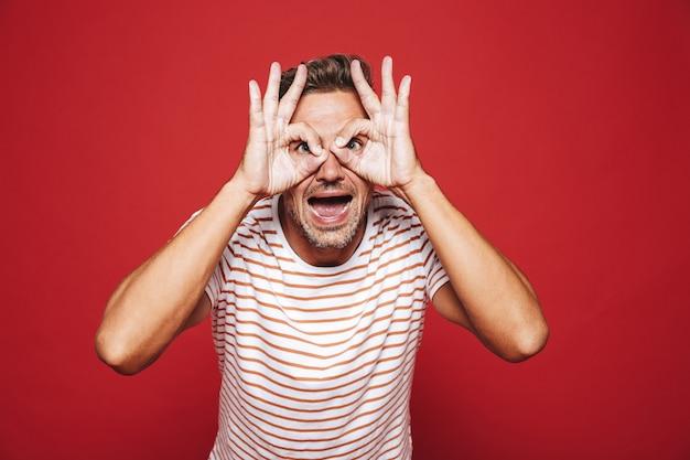 Забавный человек в полосатой футболке улыбается и смотрит сквозь дыры, сделанные пальцами, изолированными на красном