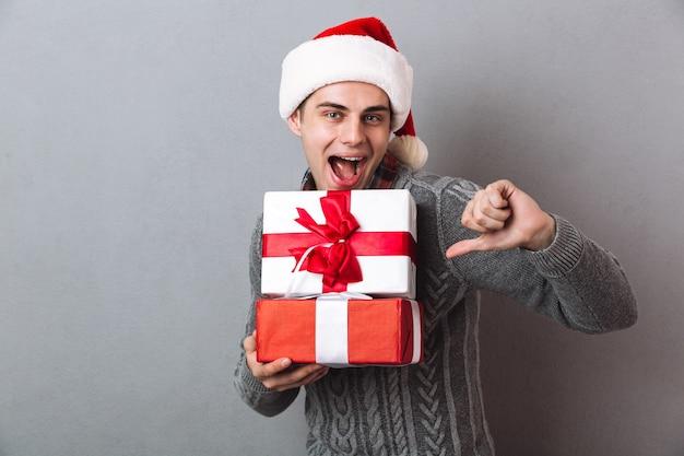Забавный человек в свитере и рождественской шапке держит подарки, показывая большой палец вниз, глядя