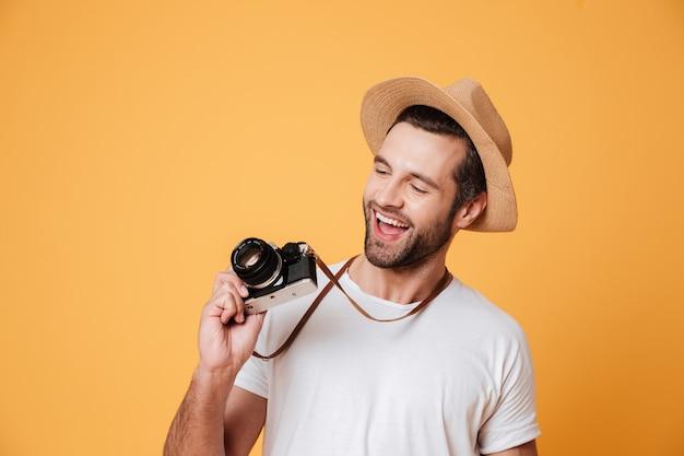 Забавный человек смотрит на старомодную ретро камеру