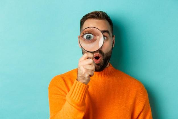 虫眼鏡を通して見て、何かを検索または調査し、ターコイズブルーの背景にオレンジ色のセーターに立っている面白い男。