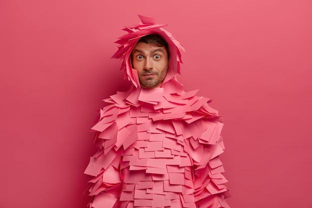 おかしな男は不思議に見え、眉を上げ、衝撃的な表情をし、ピンクの壁に隔離された粘着性のあるメモで作られた服を着ています。メモ用のバラ色のステッカーで覆われたヨーロッパの男性。