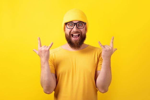 재미있는 남자는 노란색 배경 위에 로큰롤 제스처를 만듭니다.