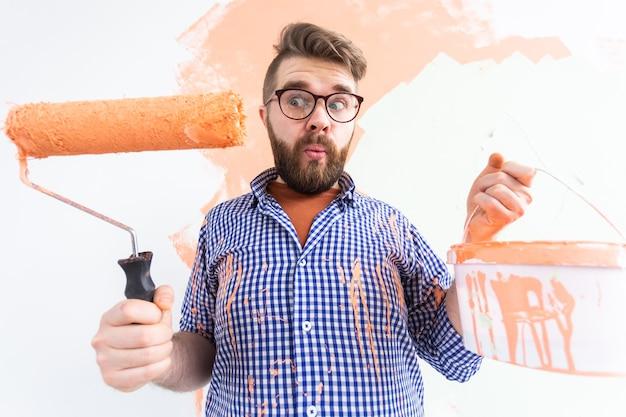 새 집에 페인트 롤러와 재미있는 남자 그림 인테리어 벽. 롤러에 페인트를 적용하는 남자는