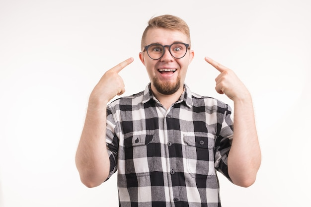 Funny man in plaid shirt points to his smiling face over white