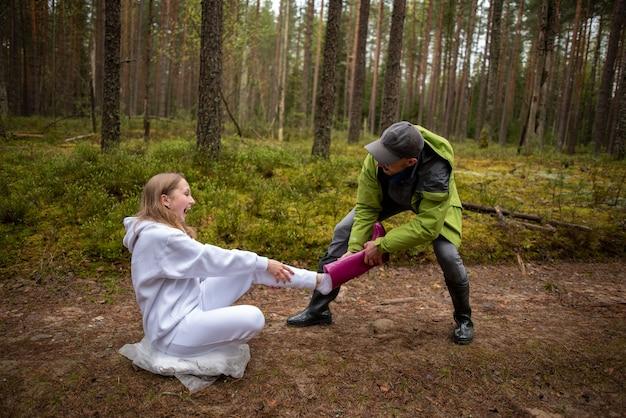 森の中で面白い女性のピンクのブーツを引っ張る面白い男
