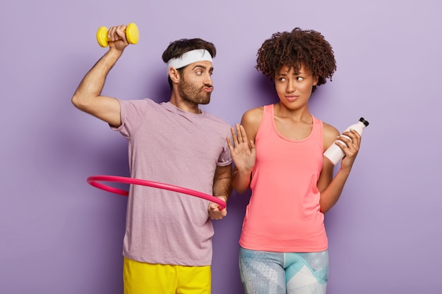 Funny man raises dumbbell, poses with hula hoop, suggests girlfriend try aerobic, dark skinned woman makes refusal gesture, holds bottle with fresh water. mixed race couple go in for sport together