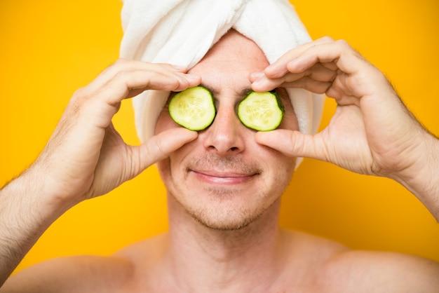 Забавный человек получает маску для лица из огурца. косметическая процедура мужское лицо. уход за собой