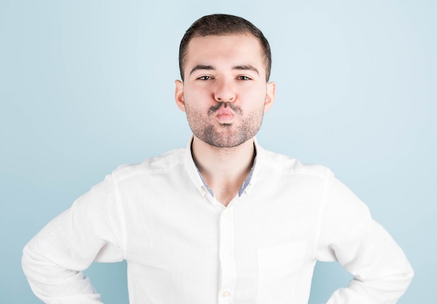 Funny man, rounds his lips, as if about to kiss someone, looks in anticipation, isolated on a blue wall. fashionable bearded man expresses positive emotions, makes a grimace