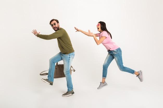 Uomo divertente scappando dalla moglie con borsa, donna che corre dietro al marito, concetto isolato