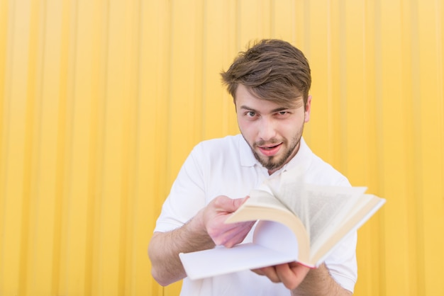 A funny man scrolls through the pages of the book on a yellow wall.