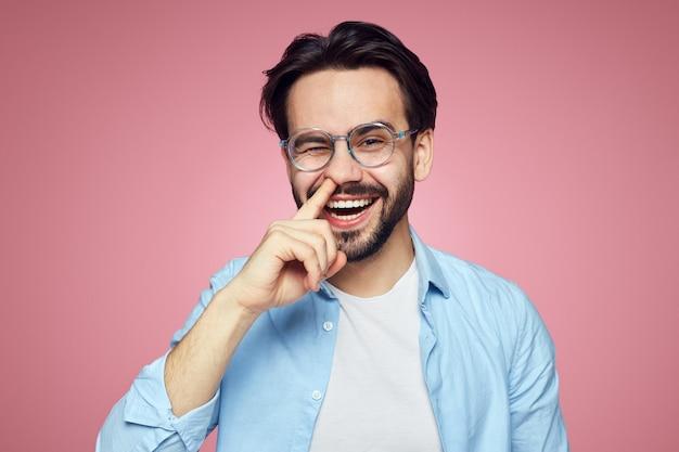 웃 고 분홍색 벽에 그의 코에 손가락을 잡고 재미있는 남자