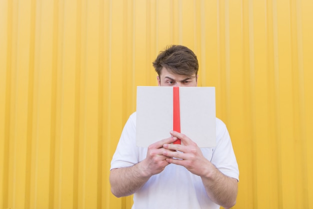 A funny man stands on a yellow wall and closes his face with a book.
