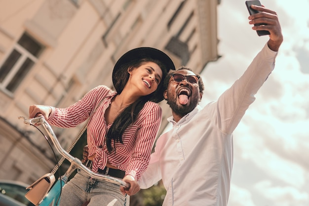 Funny man taking selfie and smiling woman sitting on the bike